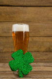 Glass of beer and shamrock for St Patricks Day. Against wooden background Stock Image