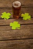 Glass of beer and shamrock for St Patricks Day. Against wooden background Royalty Free Stock Photos