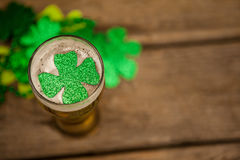 Glass of beer and shamrock for St Patricks Day. Against wooden background Royalty Free Stock Images