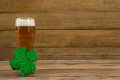 Glass of beer and shamrock for St Patricks Day. Against wooden background Royalty Free Stock Photo