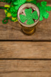 Glass of beer and shamrock for St Patricks Day. On wooden background Royalty Free Stock Photo