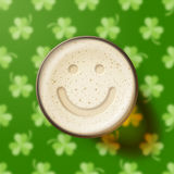 Glass of beer with smiley on clover background Stock Photo
