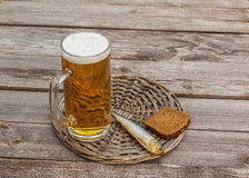 Glass of beer and smoked fish  on a wooden table Royalty Free Stock Photos