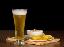 Glass of beer and snack on a black background Stock Images