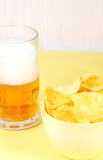 Glass of beer and snack - bowl of chips Royalty Free Stock Image