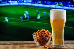Glass of beer and snack on a football game TV background. Glass of beer on a football game TV background. toning. selective focus Stock Photography