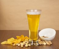 Glass of beer and a snack for him Stock Images
