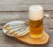 Glass of beer with a snack on a wooden table Royalty Free Stock Photography