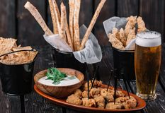 Glass of beer and snacks. Grissini, chicken grilled breast, pita chips. Glass of beer and snacks on dark wood background. Grissini, chicken grilled breast, pita royalty free stock photos