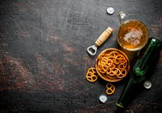 Glass of beer and snacks pretzels in the bowl royalty free stock photo