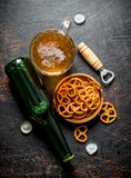 Glass of beer and snacks pretzels in the bowl stock images