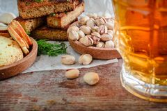 A glass of beer and snacks, rusks toast and pistachios. Glass of beer and snacks, rusks toast and pistachios on a wooden background Stock Photography