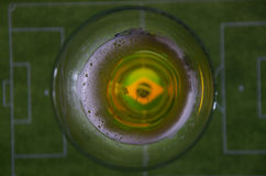 Glass of beer and soccer field. A glass of beer above a soccer field Royalty Free Stock Photography