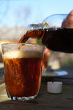 A glass of beer. Someone pours a dark beer from a bottle into a glass Royalty Free Stock Photo