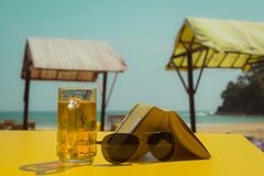 Glass of beer, sunglasses and a book  on a yellow table Stock Photos