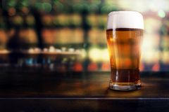 Glass of Beer on Table in Bar or Restaurant. Side View. Night Scene stock image
