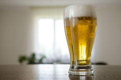 Glass with beer on the table Stock Images