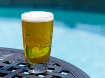 Glass of beer on table by poolside Stock Photography
