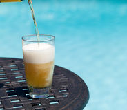Glass of beer on table by poolside. Plain pint glass of beer being poured sitting on table by blue swimming pool Royalty Free Stock Images