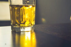 A glass of beer on the table. A glass of beer with the sunset light shining it royalty free stock image