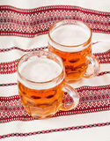 A glass of beer on the tablecloth. Stock Photos