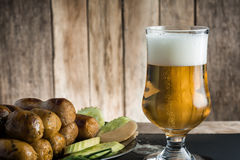 Glass of beer and thai sausage on wooden table. Royalty Free Stock Images