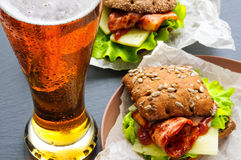 Glass of beer and two burger-like sandwiches with lettuce, bacon, cheese, ketchup on paper, black slate stone Royalty Free Stock Photo