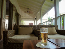 Glass of Beer on the Veranda. A refreshing cool glass of beer sits on a table on the veranda of a resort in Barbados Stock Image