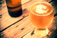 Glass of beer. Vintage retro style and soft focus,Glass of beer on wood table Royalty Free Stock Photo