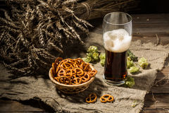Glass beer with wheat and hops, basket of pretzels Royalty Free Stock Photos