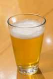 A glass of beer. On the wood table stock images