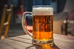 Glass of beer on a wood table. Glass of cold beer on a wood table royalty free stock image
