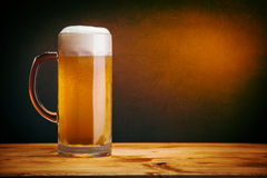 Glass of beer. On wood table with grunge wall Stock Image