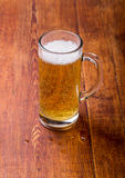 Glass of beer on the wooden grunge table Royalty Free Stock Images