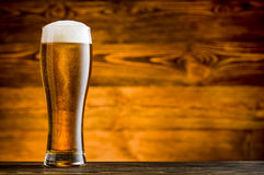 Glass of beer on wooden table Royalty Free Stock Photo