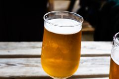Glass of beer on the wooden table. Draft beer served at the bar. Glass of light beer on the wooden board. Served alcoholic drinks. Glass of beer on the wooden stock photos