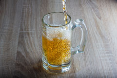 Glass of beer on a woody background. Glass of beer on a woody table stock images