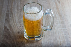Glass of beer on a woody background Stock Photo