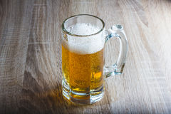 Glass of beer on a woody background. Glass of beer on a woody table stock photography