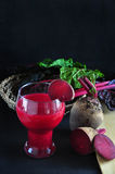Glass of Beetroot Juice with Fresh Beetroot on Black Background Royalty Free Stock Images