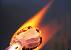 The glass begins to take shape in the heat of the torch. The glass softens in the beadmaker's flame Stock Photo