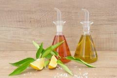 Glass behållare med olivolja och vinäger, salt hav, citron på en träbakgrund Traditionell grekisk mat arkivbilder