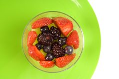 Glass of berries on green plate Royalty Free Stock Photos