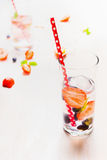 Glass with berries lemonade, ice cubes and red straw on white wooden background Royalty Free Stock Photo