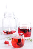 Glass of berry drink with fresh fruits on marble table Stock Photos