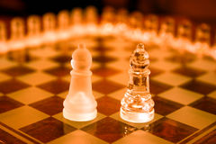 Glass bishop chess pieces. Two glass bishop chess pieces on a glossy game board Royalty Free Stock Image
