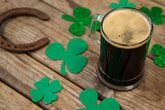 Glass of black beer, horseshoe and shamrock for St Patricks Day Royalty Free Stock Photos