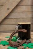 Glass of black beer, horseshoe and shamrock for St Patricks Day Stock Photo