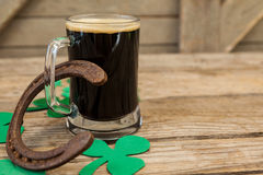 Glass of black beer, horseshoe and shamrock for St Patricks Day Stock Photography