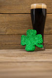 Glass of black beer and shamrock for St Patricks Day Royalty Free Stock Images